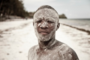 A boy covered in sand on Bamburi beach, Mombasa, Kenya